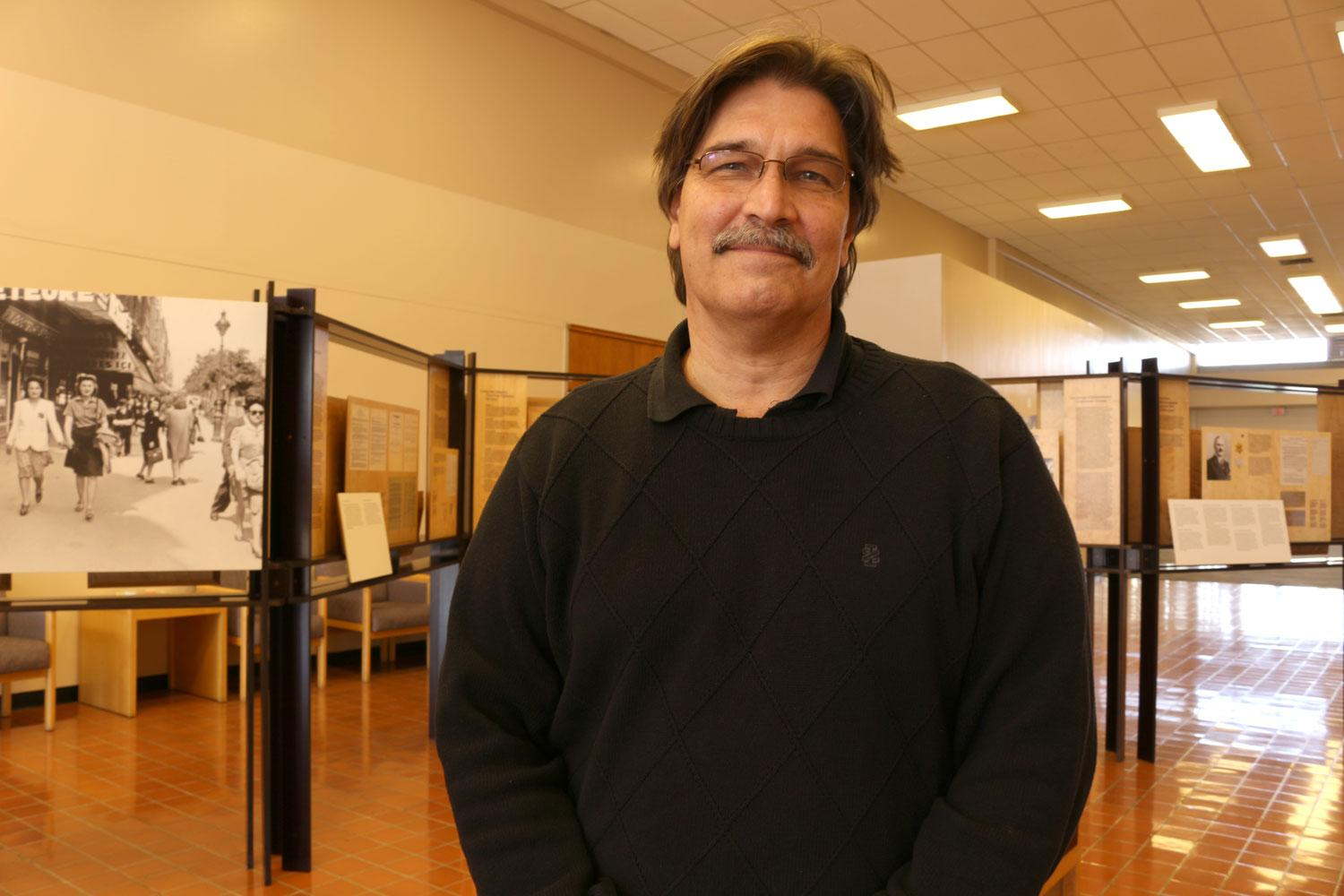SCC professor John Liffiton stands in front of the Hélène Berr exhibit in the school's Student Center. The exhibit is part of the school's upcoming Genocide Conference for Genocide Awareness Week.