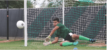 Freshman goalkeeper Luis Hector Hernandez dives and blocks a potential goal during practice.