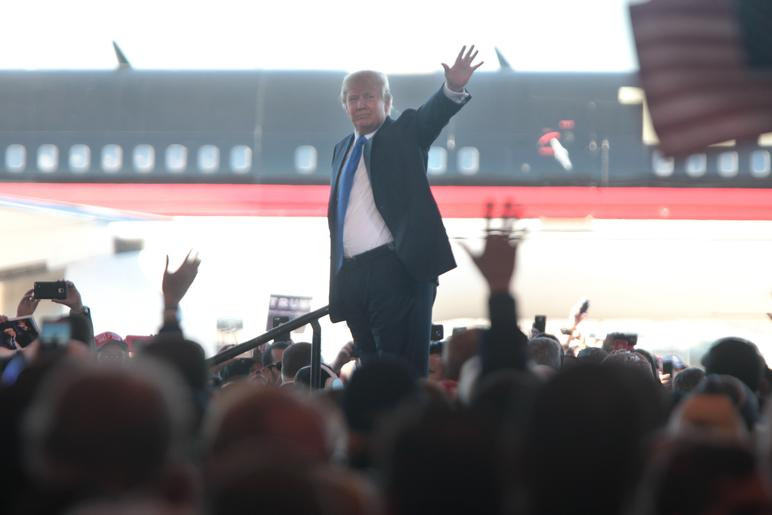 Donald Trump waving to supporters at a hangar at Mesa Gateway Airport in Mesa, Ariz.