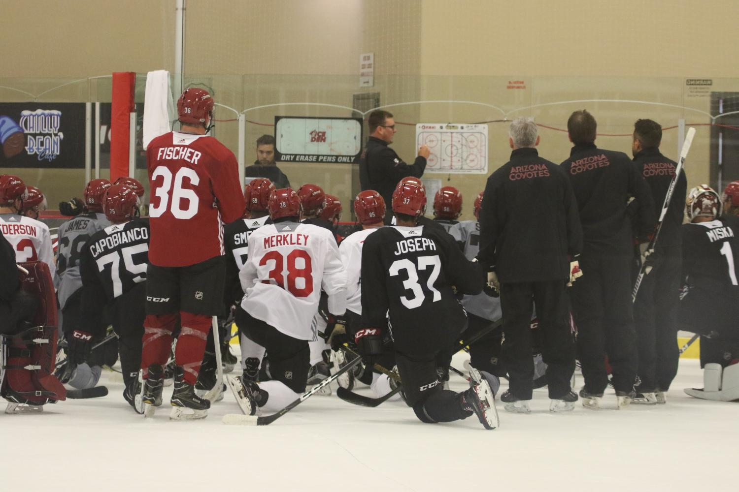 Coyotes rookies take a knee between drills to talk with Head Coach Mike Van Ryn of the Tucson Roadrunners on Sept. 8