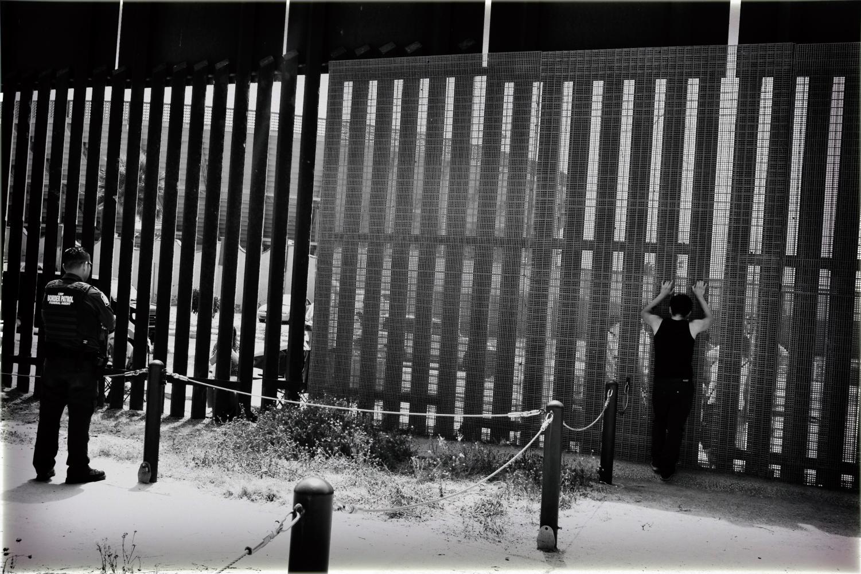 Border+Patrol+agent+looks+into+Mexico+from+the+U.S.-Mexico+border+near+San+Diego%2C+California
