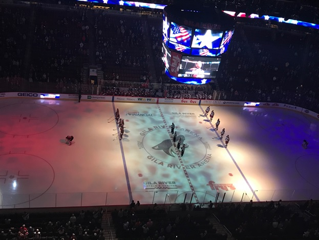 Arizona Coyotes and Columbus Blue Jackets stand during the National Anthem.