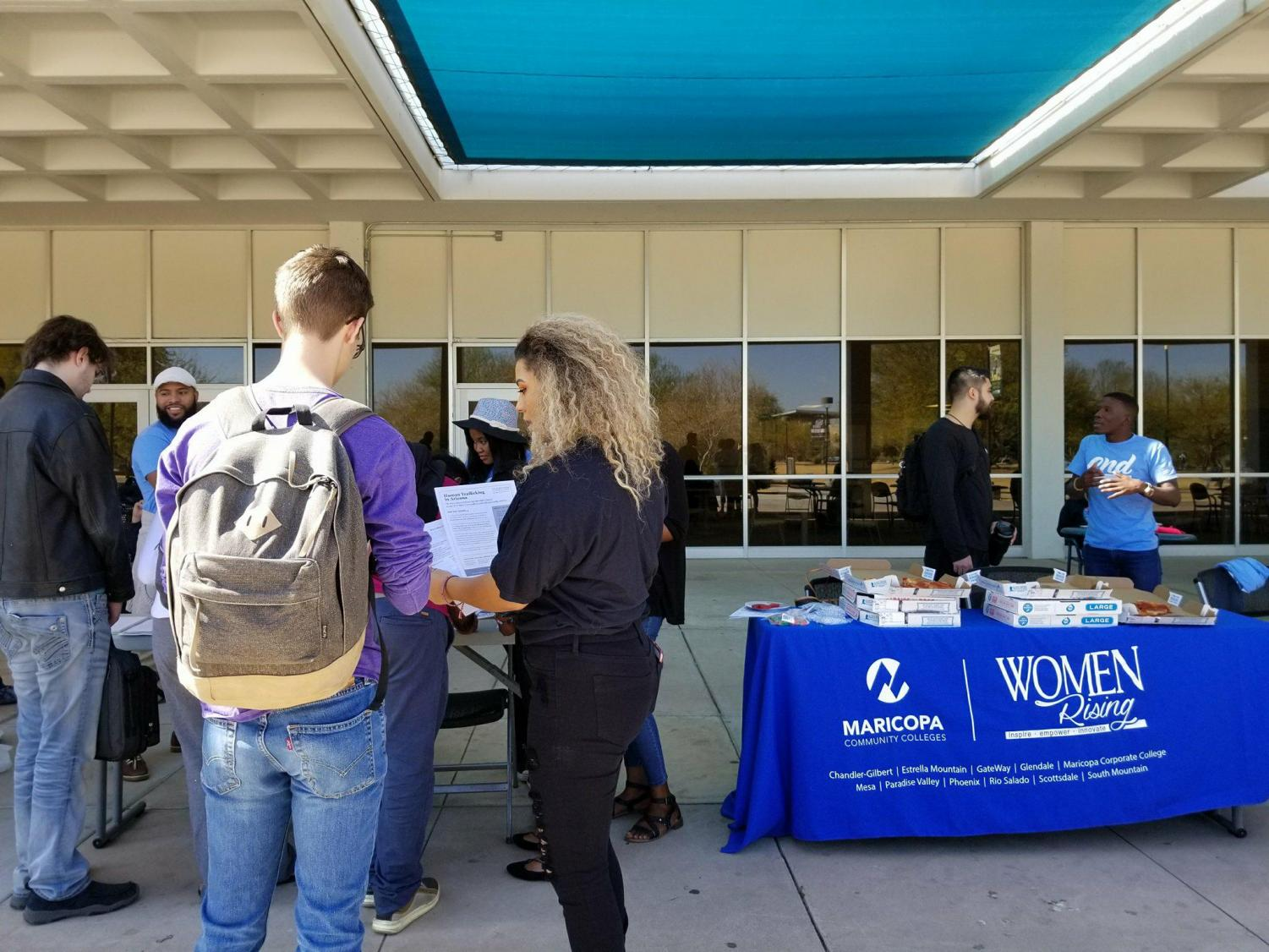 Students gathered around the human trafficking awareness event tables outside of the student center.