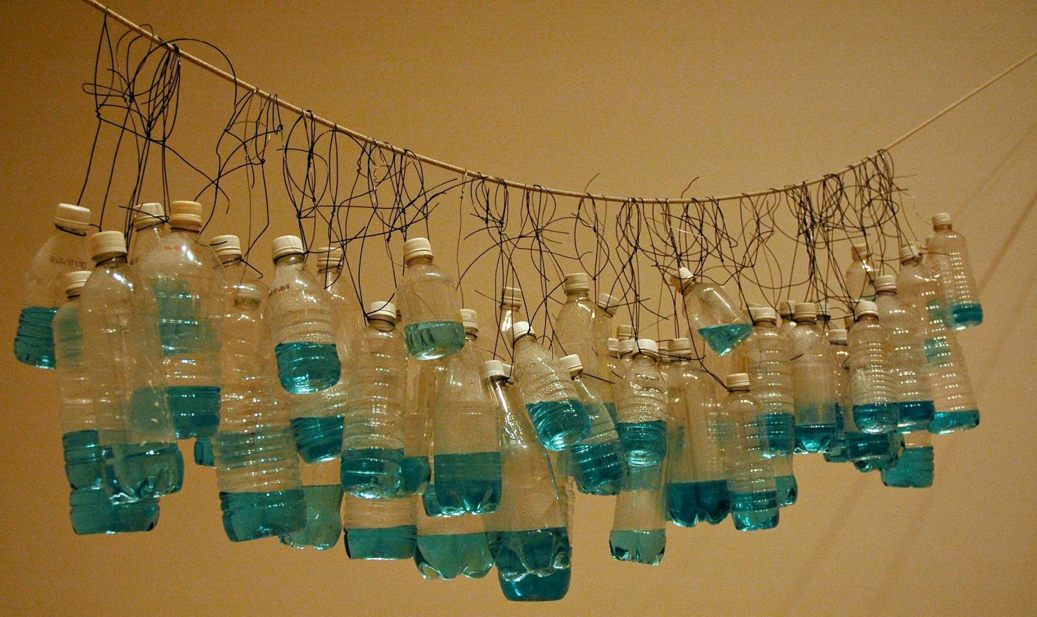 Empty plastic water bottles hung from a wire.