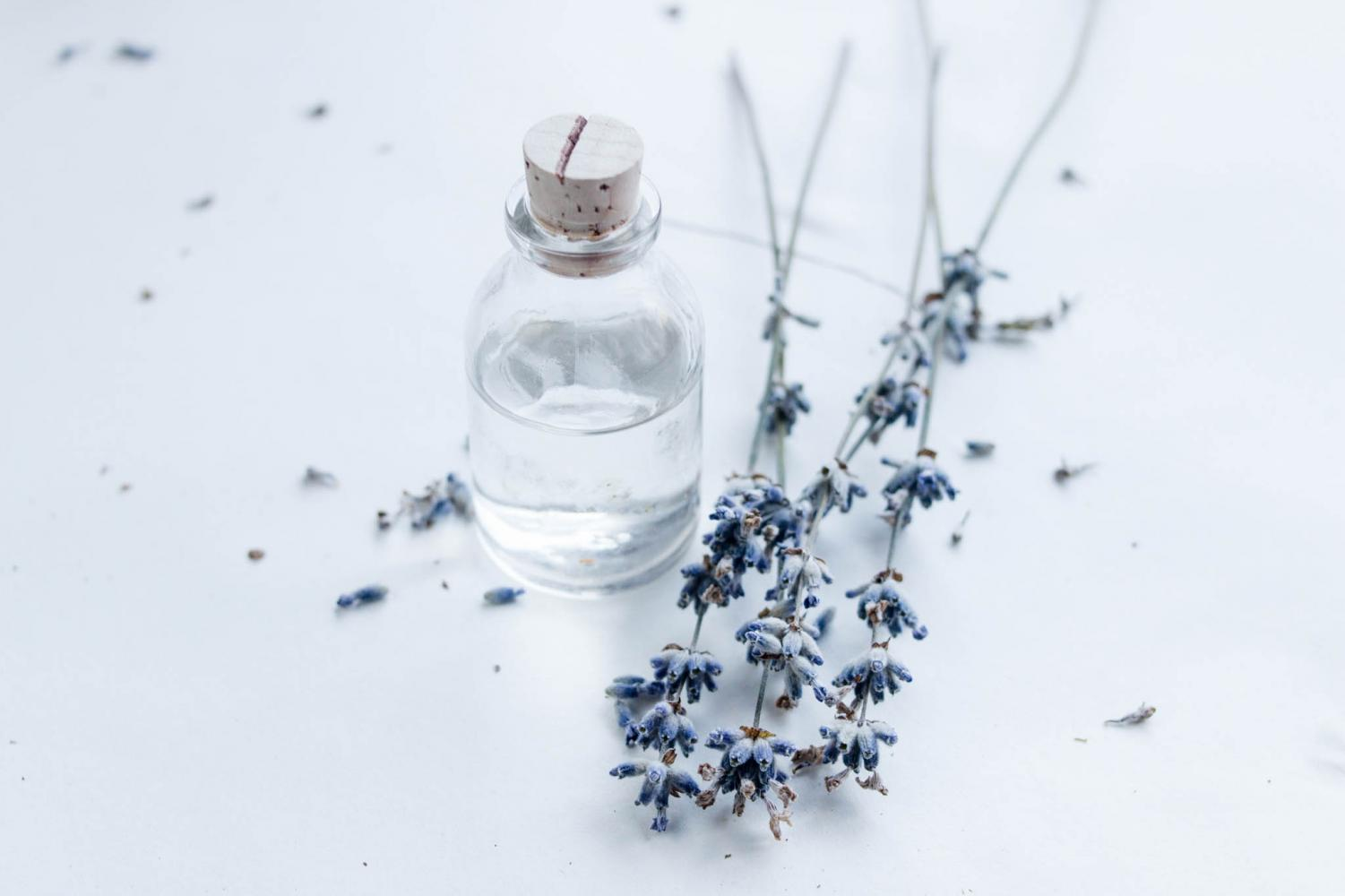 A small water jar next to lavender.
