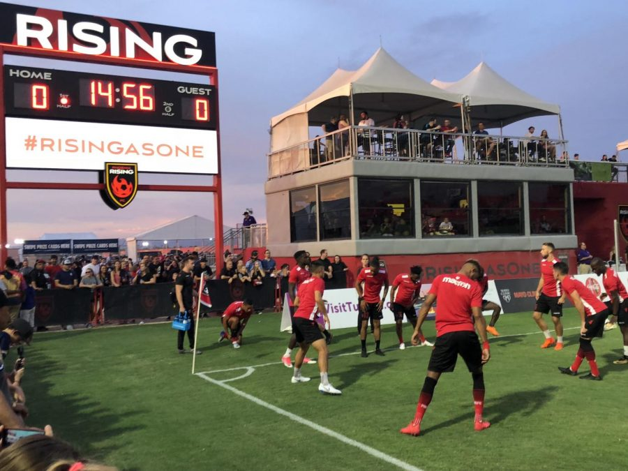 Jake Anderson takes photograph of Phoenix Rising players during warm-ups