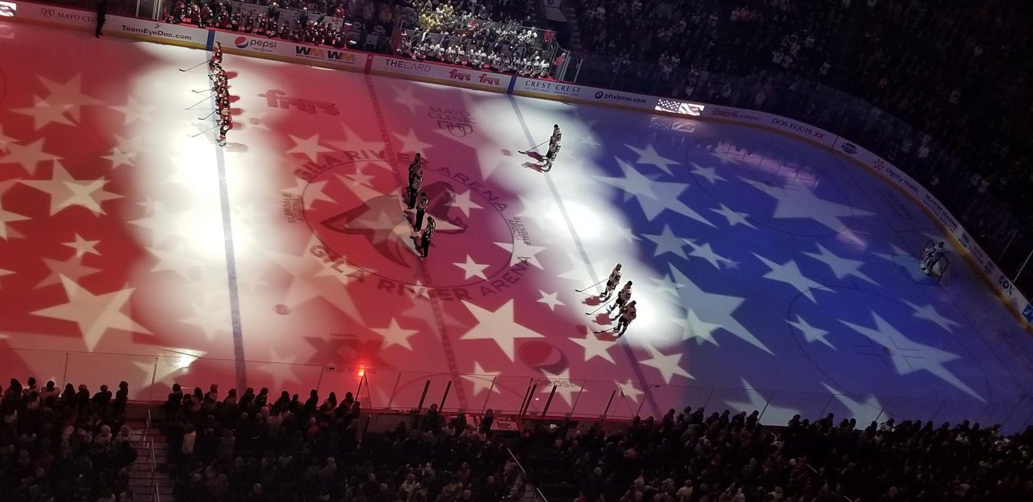 The Coyotes and Golden Knights stand during the national anthem at Gila River Arena.
