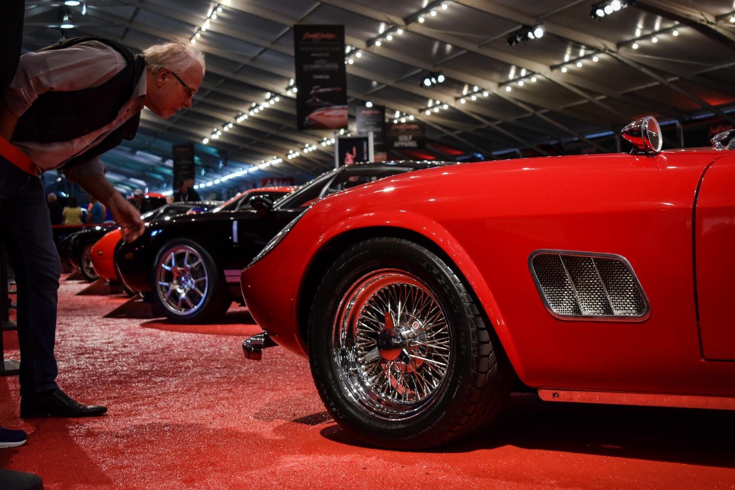 A prospective buyer inspects one of the collector cars for auction