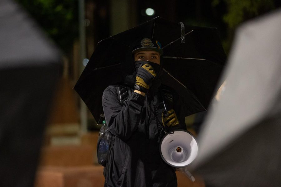 Darien Barrett speaks to the crowd of protesters about the night's plan and why they are gathered.