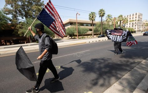Protesters walk down Central Ave into oncoming traffic with an upside-down American flag, the universal symbol for distress or great danger.